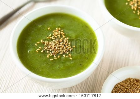 Fresh cream of zucchini soup with toasted sesame seeds on top served in bowls photographed with natural light (Selective Focus Focus in the middle of the soup)