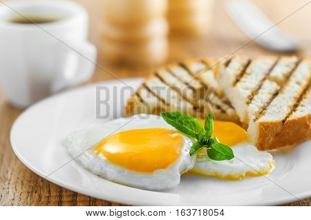 Fried eggs with toasts and coffee traditional breakfast