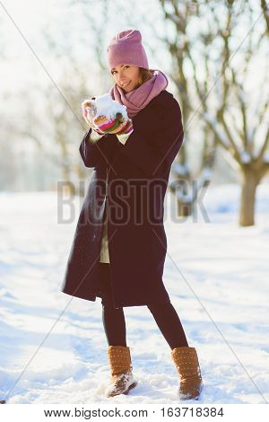 season, christmas, holidays and people concept - smiling young woman in winter clothes outdoor.