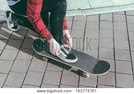 Young man in shirt tying a shoelaces on the street