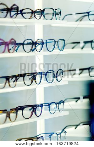 POV of customer looking at multiple eyeglasses frames in optical store - admiring the different shapes and coloro and diverse glass materials