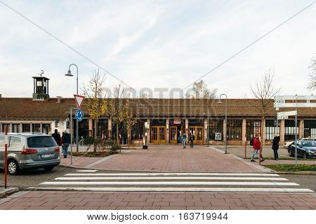 FREUDENSTADT GERMANY - NOV 20 2016: Deutsche Bahn train station facade with commuters and cars in the calm city of Freudenstadt in Baden-Wurttemberg Germany