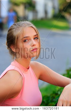 Pretty young woman or girl with tied in bun blonde hair in pink shirt with cute serious face on blurred background