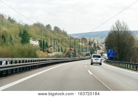 GERMANY - MAR 26 2016: Driver point of view pov of white Volkswagen van driving on German Autobahn Bundesautobahn or Federal Motorway highway with speed limits of 100 kmh electronic street sign