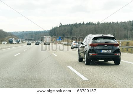 GERMANY - MAR 26 2016: Driver point of view pov of black Kia Sportage SUV driving on German Autobahn Bundesautobahn or Federal Motorway highway with speed limits of 100 kmh electronic street sign