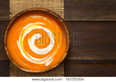 Fresh homemade cream of carrot soup with a swirl of cream on top served in wooden bowl photographed overhead on dark wood with natural light (Selective Focus Focus on the soup)