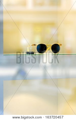 Trendy fashion sunglasses in window store with price tag on yellow background