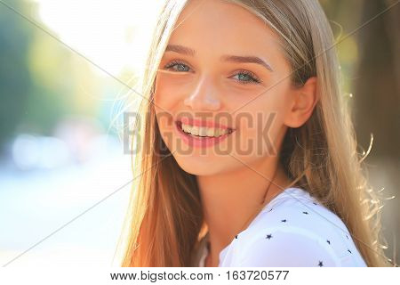 Pretty young woman or girl with long blonde hair in white blouse with stars and cute smiling face in sunny summer day