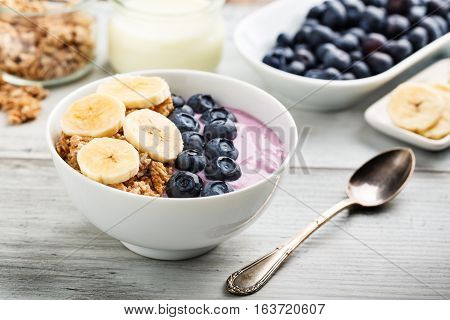 Cereals with bananas, fresh blueberries and yogurt.