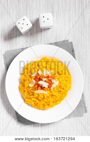 Fresh homemade carrot risotto made with pureed carrot garnished with roasted carrot and hard cheese photographed overhead with natural light (Selective Focus Focus on the top of the risotto)