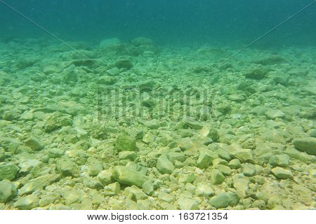 Underwater seafloor with stones cobblestones and clear blue water background.