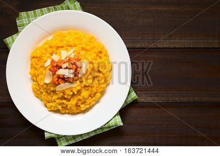 Fresh homemade carrot risotto made with pureed carrot garnished with roasted carrot and hard cheese photographed overhead on dark wood with natural light (Selective Focus Focus on the risotto)