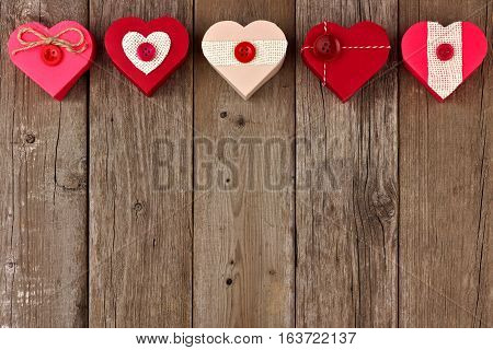 Valentines Day Top Border Of Heart Shaped Gift Boxes With Red And Burlap Trim Over Wood