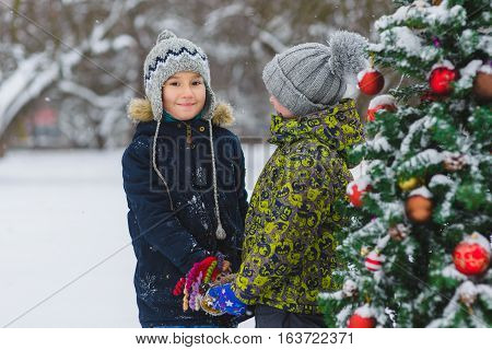 Two happy boys or a friends near Christmas tree outdoor.