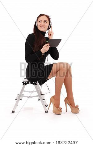 Happy student teenage girl sitting on the ladder with tablet pc at headphones isolated on white
