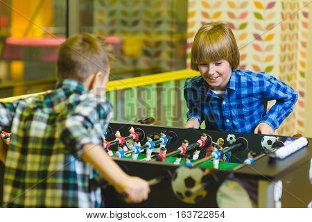 Happy boys playing table football in children room.