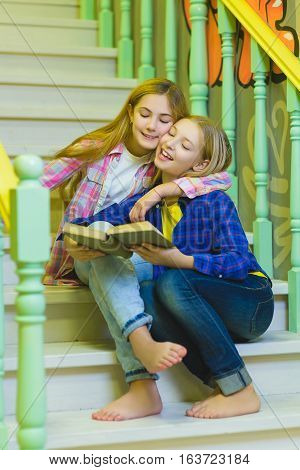 cute girls with holding book and sitting on stairs of ladder indoor.