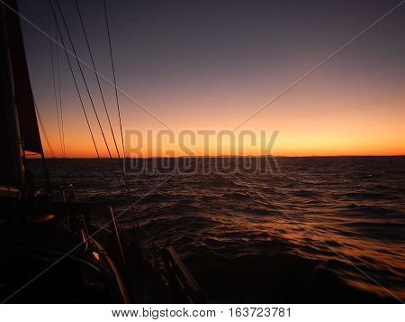 Dusk aboard an ocean sailing vessel at sea.