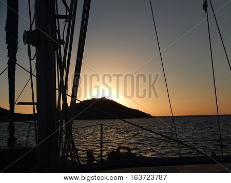Approaching an island sunset on a sailboat at sea.