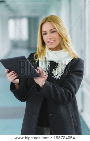 fashion business woman dressed in coat looking at tablet in hall.