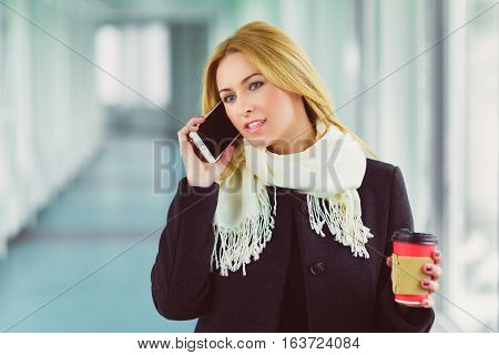 Happy fashion woman using smart phone and holding take away coffee in hall.