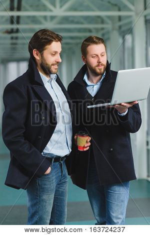 Two handsome businessmen working together on a project at lobby.
