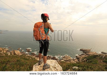 successful hiker use cellphone taking photo on seaside mountain peak rock