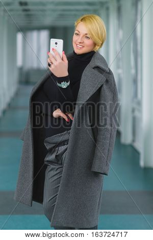 fashion business woman dressed in coat looking at smart phone in hall.