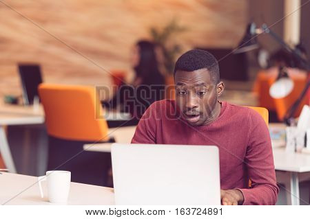 Young business man with a shocked expression working on a laptop.