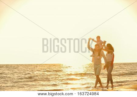 happy young family have fun on beach run and jump at sunset.