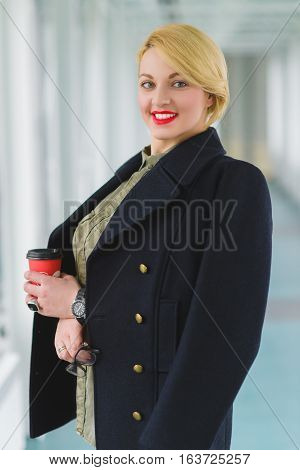 Portrait of blond businesswoman holding coffee and glass in lobby.