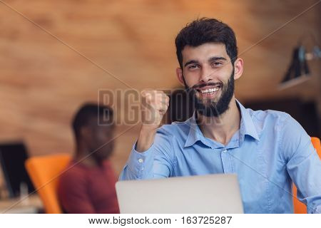 Young bearded caucasian modern business man sitting in a startup office using laptop, looking downward the screen, smiling - business, work, technology concept.