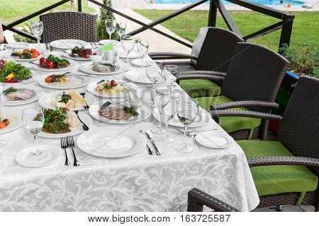 Cutlery and cold cuts served on a festive table in restaurant outdoors, snacks on the holiday table