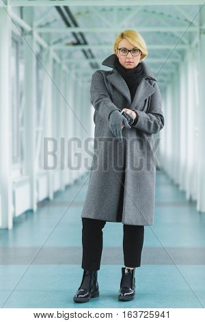 fashion elegant woman dressed coat stand in lobby.