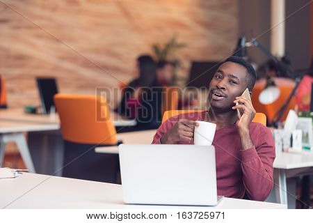 African American businessman on the phone sitting at the computer in his startup office