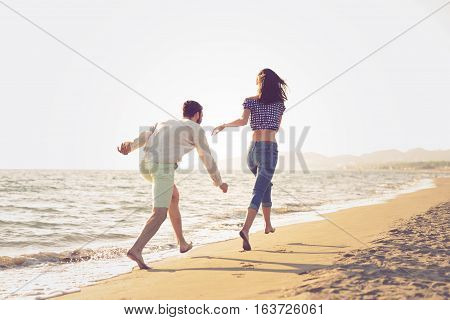 happy young couple running on the beach