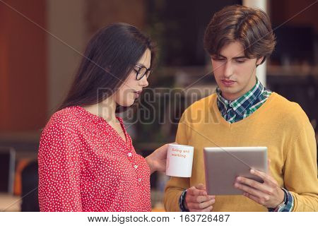Businesspeople using tablet computer, talking in office