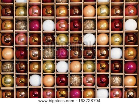 Box of colorful holiday decorative glass balls creates a background grid pattern in a box