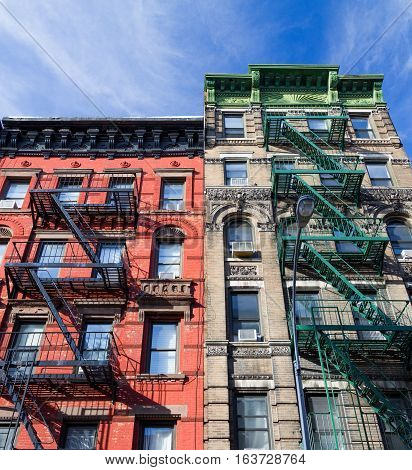 Colorful old vintage apartment buildings with fire escapes in the Greenwich Village neighborhood of Manhattan in New York City NYC