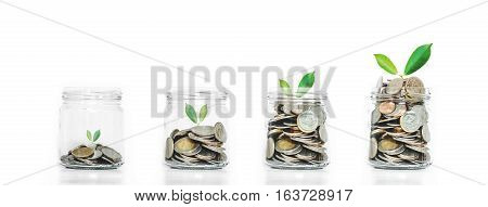 Money saving growth concepts, glass jar with coins and plants growing, isolated on white background