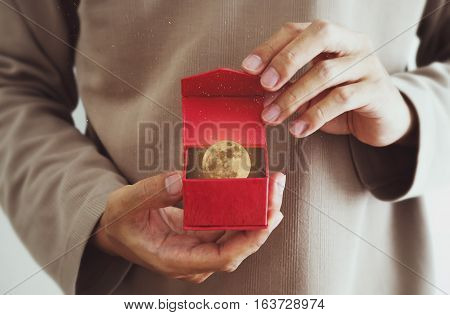Close-up a man opening red gift box, with the moon and stars inside, vintage tone