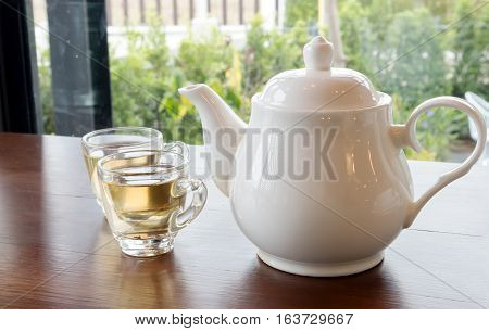 Tea pot and cups of tea on wood table with nature background