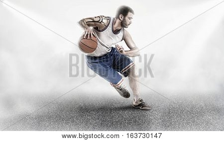 basketball player with ball on asphalt in lights and white fog