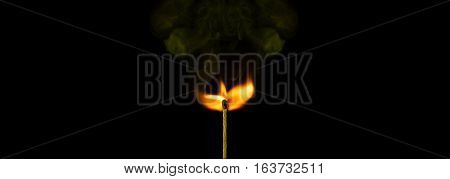 Macro of a burning matchstick flame in the dark.