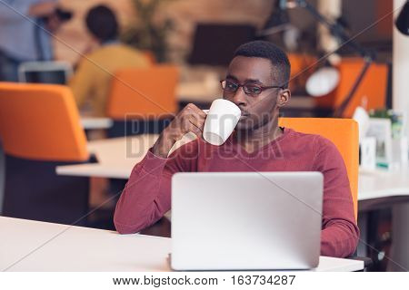 Startup business with laptop. Cheerful young African businessman typing looking on laptop.