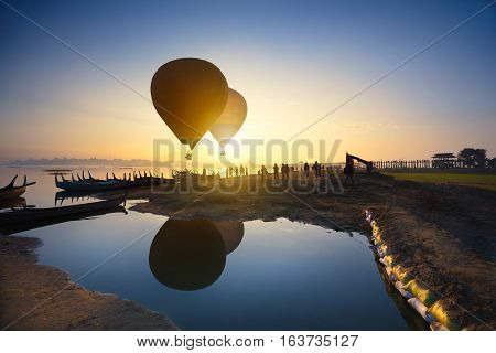 Sunrise at U Bein Bridge with boat and hot air balloon Mandalay Myanmar