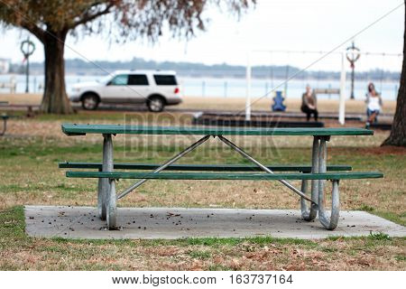 Green wooden picnic table on a cement slab in a park setting for a picnic