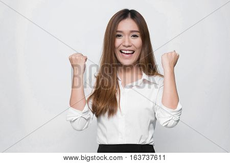 Excited success young Asian woman with arms up. Celebrating success concept.