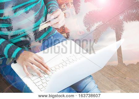 Technology shopping banking home and lifestyle concept - Double exposure of female with laptop computer and credit card and palm tree