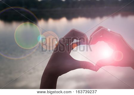 Hand in shape of love heart with sunset reflaction background